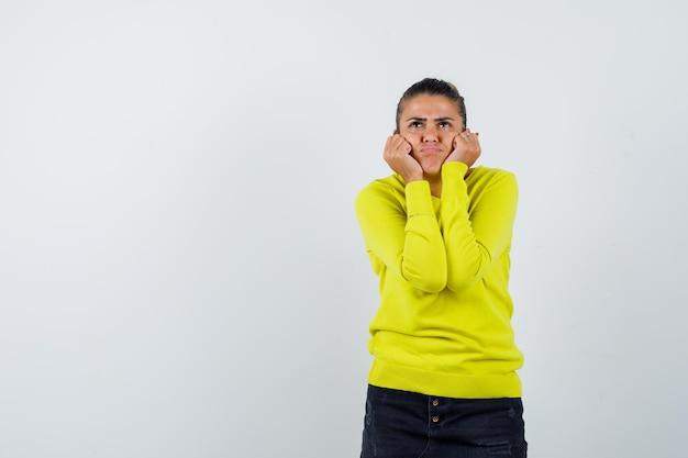 Jonge vrouw die haar handen op de wangen legt, naar boven kijkt, aan iets denkt in een gele trui en zwarte broek en peinzend kijkt