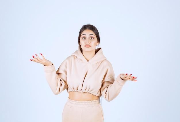 Jonge vrouw die haar handen opent, iets vraagt of aanbiedt
