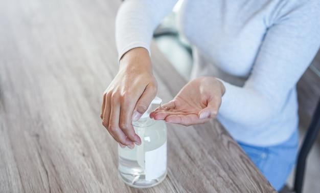 Jonge vrouw die haar handen schoonmaakt met ontsmettingsgel voor preventie van coronavirus - hygiëne om verspreiding van het covid 19-concept te stoppen - focus op linkerhand