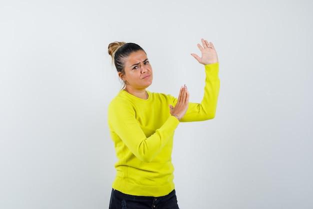 Jonge vrouw die haar handen uitstrekt terwijl ze iets vasthoudt, grimassen trekt in gele trui en zwarte broek en er gehaast uitziet
