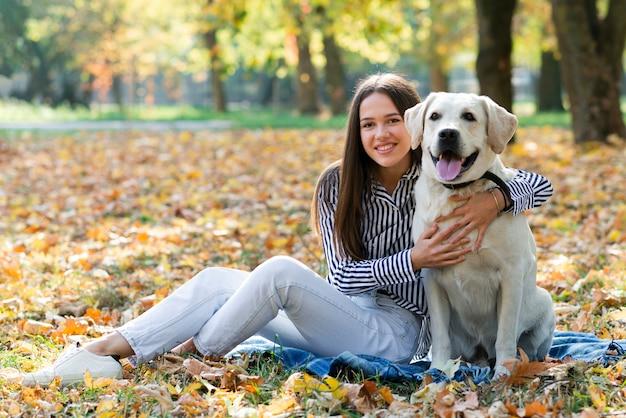 Jonge vrouw die haar hond koestert