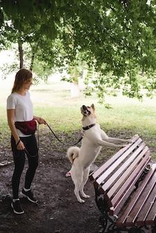 Jonge vrouw die haar hond uitlaat in een park