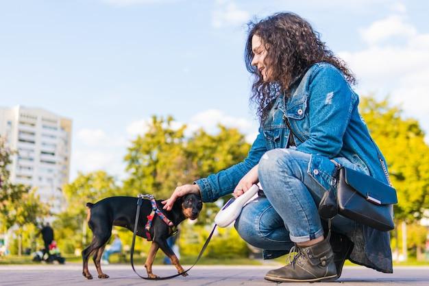 Jonge vrouw die haar hondje buiten speelt en traint. black and tan dwergpinscher vrouwelijke hond met eigenaar in een park