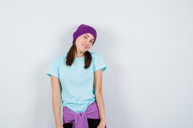 Jonge vrouw die haar hoofd buigt terwijl ze poseert in blauw t-shirt, paarse muts en er gelukkig uitziet, vooraanzicht.