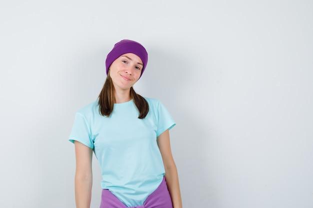 Jonge vrouw die haar hoofd buigt terwijl ze poseert in blauw t-shirt, paarse muts en er vrolijk uitziet, vooraanzicht.