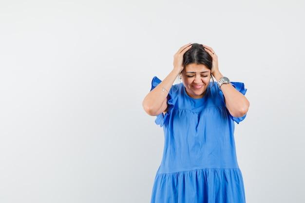Jonge vrouw die haar hoofd in handen in blauwe jurk klemt en er gelukzalig uitziet