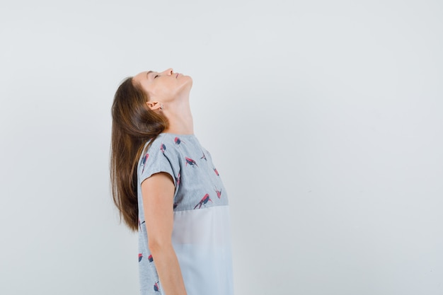 Jonge vrouw die haar hoofd in t-shirt achterover kantelt en ontspannen kijkt. vooraanzicht.