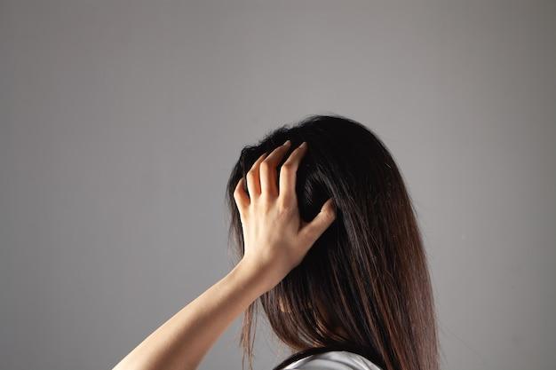 Jonge vrouw die haar hoofd krabt