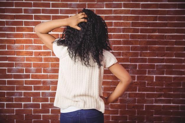 Jonge vrouw die haar hoofd krast