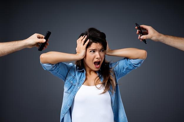 Jonge vrouw die haar hoofd vasthoudt en schreeuwt omdat ze een telefoontje moet beantwoorden.