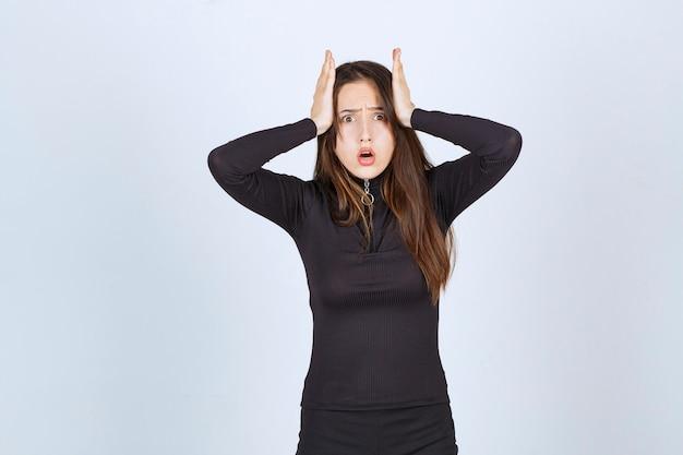 Jonge vrouw die haar hoofd vasthoudt omdat ze hoofdpijn heeft of opgewonden werd