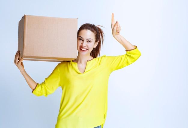 Jonge vrouw die haar kartonnen pakje vasthoudt en introduceert Gratis Foto
