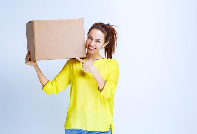 Jonge vrouw die haar kartonnen pakje vasthoudt en introduceert