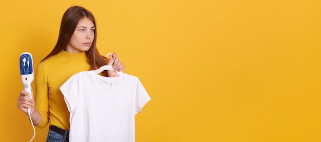 Jonge vrouw die haar kleren stomen die thuis, stoomstrijkijzer en witte t-shirt op hangers in handen houden, kijkend opzij met ernstige blik, die tegen gele muur stellen.