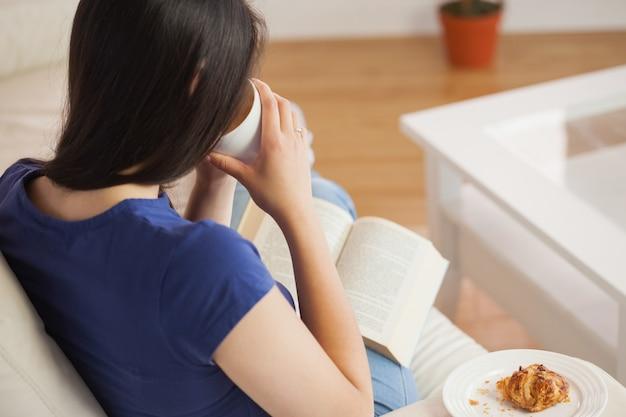 Jonge vrouw die haar koffie nipt en boek leest