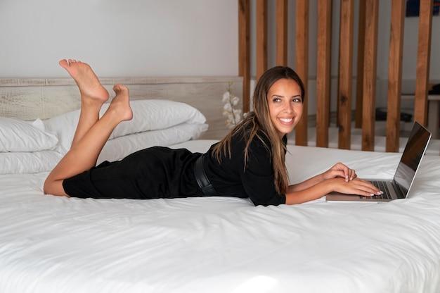 Jonge vrouw die haar laptop in een hotelkamer controleert terwijl ze op reis is