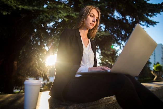 Jonge vrouw die haar laptop laag hoekschot bekijkt