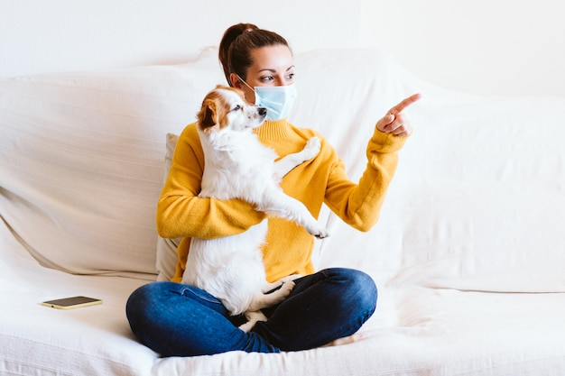 Jonge vrouw die haar leuke kleine hond thuis koestert, zittend op de laag, beschermend masker draagt. blijf thuis concept tijdens coronavirus covid-2019