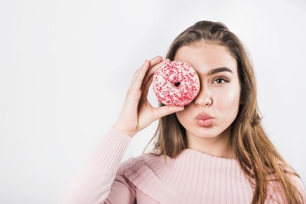 Jonge vrouw die haar lippen pruilt die haar ogen behandelen met doughnut op witte achtergrond