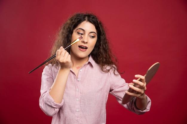 Jonge vrouw die haar make-up met borstel toepast.