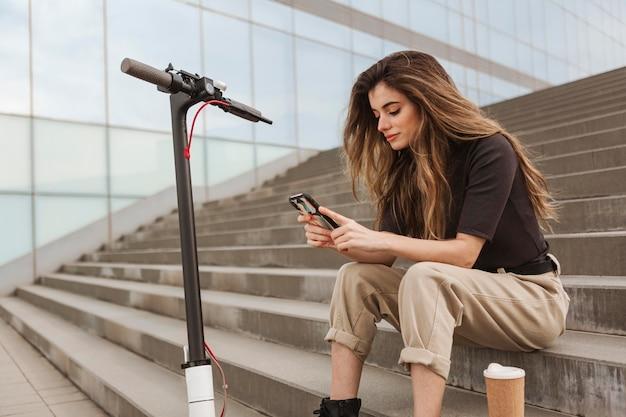 Jonge vrouw die haar mobiele telefoon doorbladert