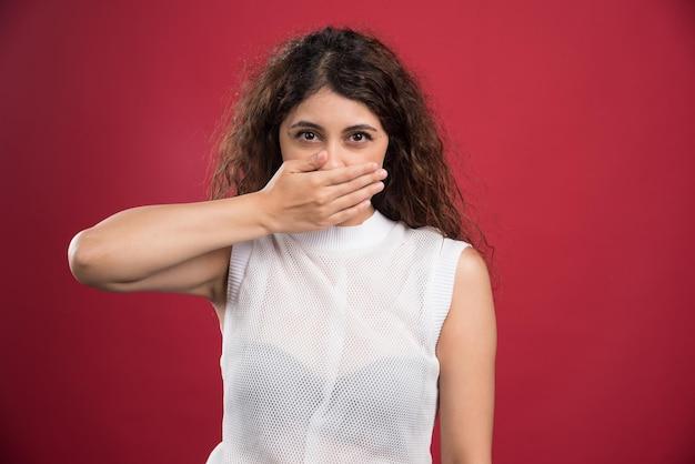 Jonge vrouw die haar mond op een rood bedekt.