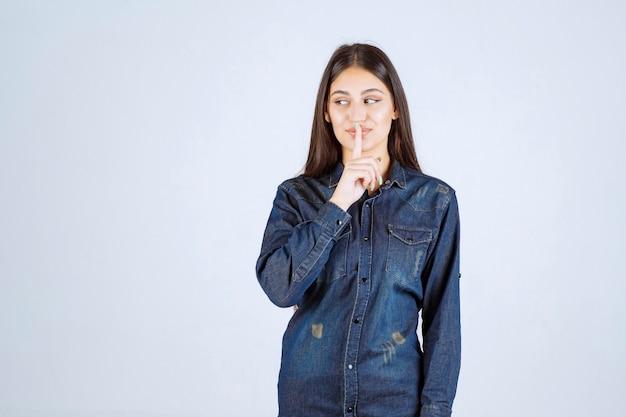 Jonge vrouw die haar mond richt en om stilte vraagt