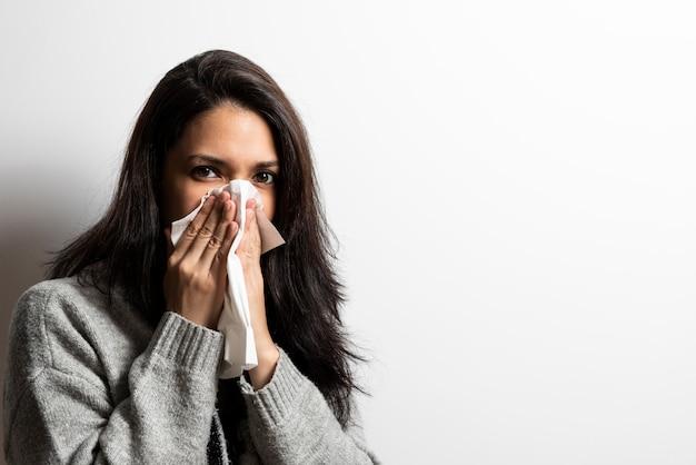 Jonge vrouw die haar neus blaast