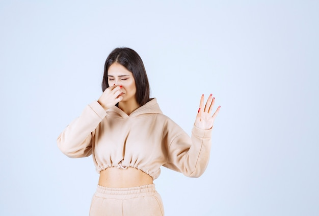 Jonge vrouw die haar neus houdt en slechte geur probeert te stoppen
