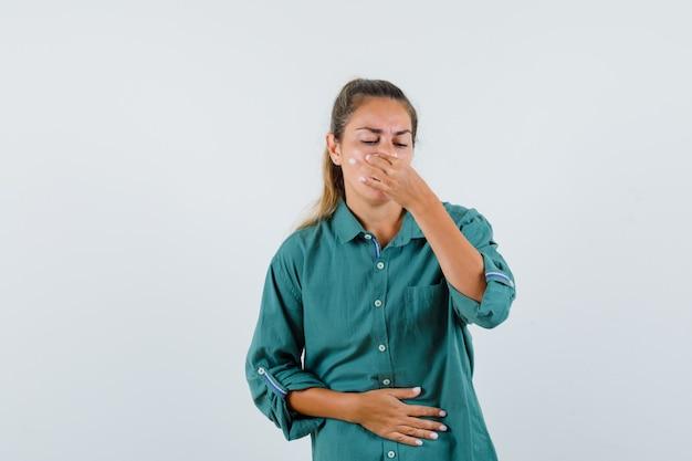 Jonge vrouw die haar neus in blauw overhemd knijpt en walgt kijkt