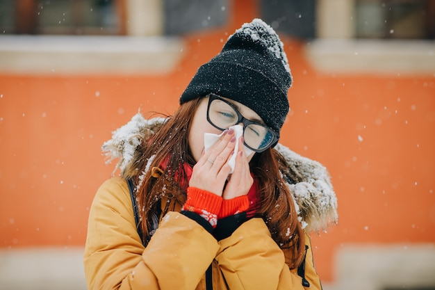 Jonge vrouw die haar neus in een weefsel in de winter blaast