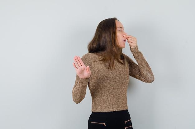 Jonge vrouw die haar neus knijpt terwijl ze iets in gouden blouse afwijst en walgt