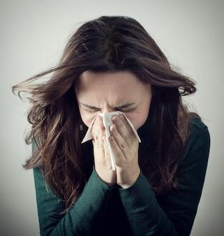 Jonge vrouw die haar neus met papieren zakdoekje blaast.