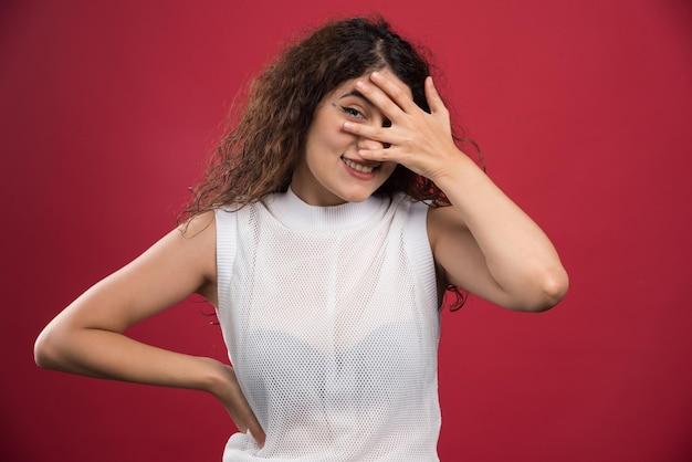 Jonge vrouw die haar ogen bedekt met haar hand op rood.