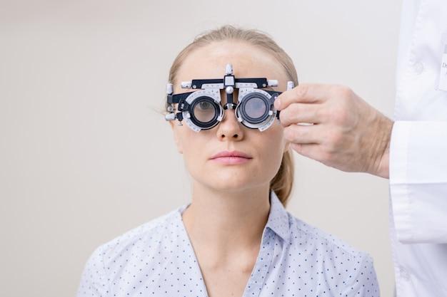 Jonge vrouw die haar oogvisie heeft onderzocht terwijl zij door optometrische lens in klinieken kijkt