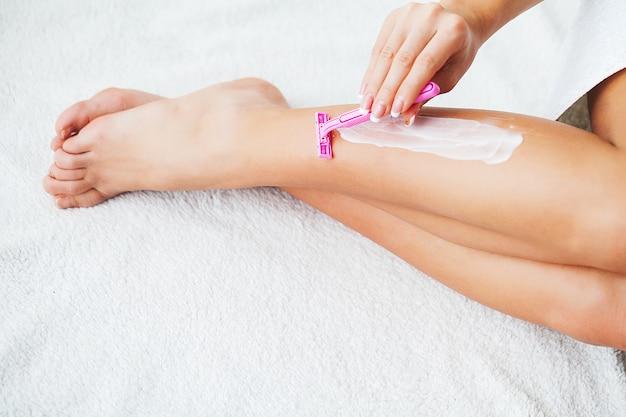 Jonge vrouw die haar op benen met scheermes verwijdert. lichaamsverzorging en scheren elke dag. gladde huid