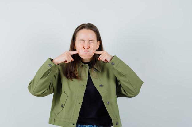 Jonge vrouw die haar opgeblazen wangen in groene jas, vooraanzicht knijpt.