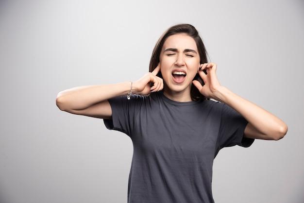 Jonge vrouw die haar oren behandelt over een grijze achtergrond.