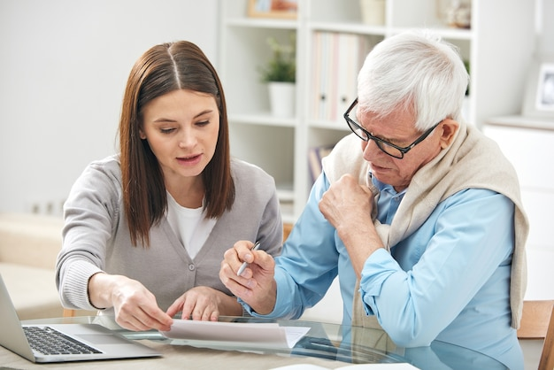 Jonge vrouw die haar oudste vader uitlegt hoe ze papier moet invullen terwijl ze hem al zijn punten en velden laat zien