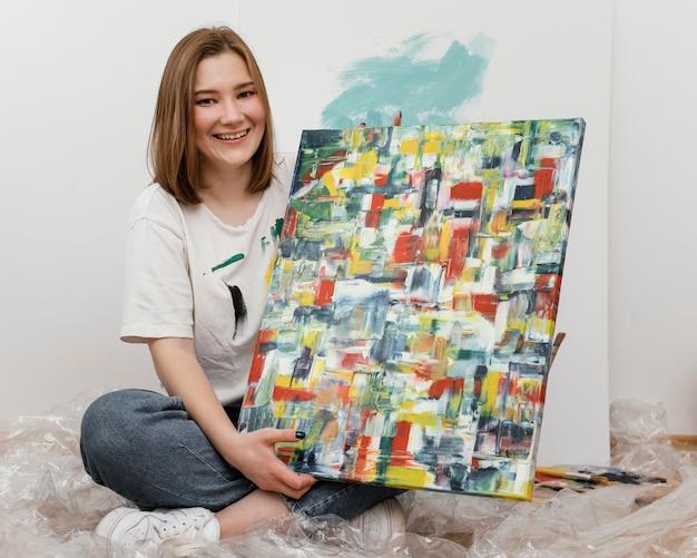 Jonge vrouw die haar schilderij toont