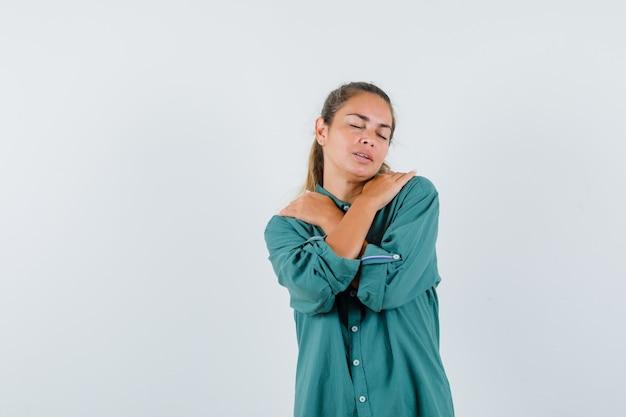 Jonge vrouw die haar schouders in blauw overhemd masseert en ontspannen kijkt