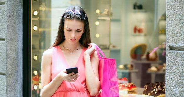 Jonge vrouw die haar smartphone gebruikt terwijl het winkelen in een stad