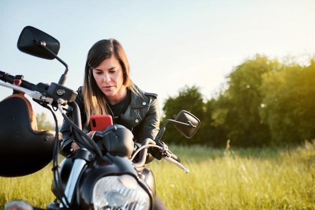 Jonge vrouw die haar smartphone gebruikt terwijl ze op een motorfiets zit