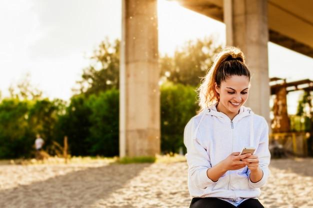 Jonge vrouw die haar sociale netwerkstatus actualiseert terwijl het ontspannen bij het strand