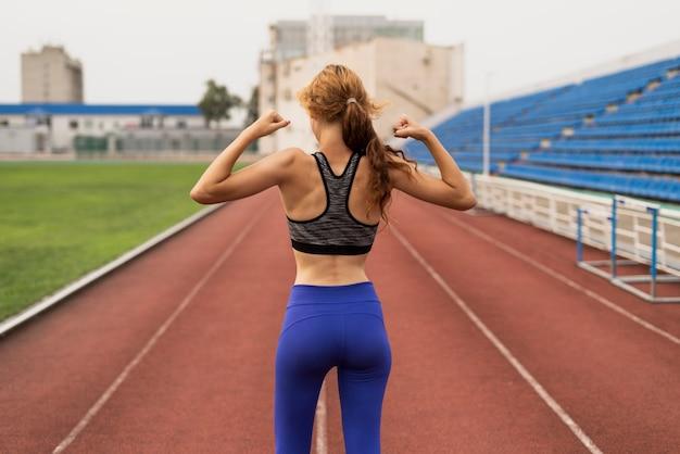 Jonge vrouw die haar spieren toont
