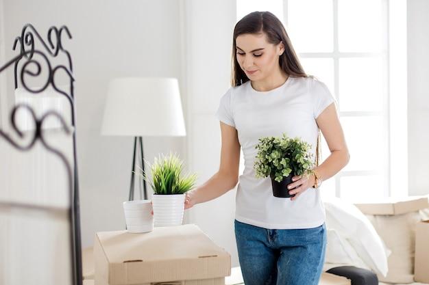 Jonge vrouw die haar spullen in een nieuw appartement plaatst