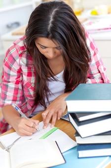 Jonge vrouw die haar thuiswerk doet