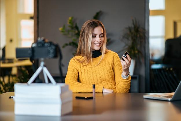 Jonge vrouw die haar videoblog over nieuwe kosmetische producten registreert.