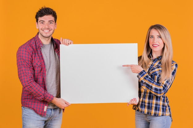 Jonge vrouw die haar vinger op aanplakbiljetholding richten door zijn vriend tegen oranje achtergrond