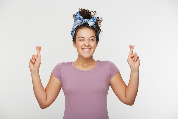 Jonge vrouw die haar vingers kruist en veel geluk wenst. geïntrigeerde vrouw in t-shirt beet op haar onderlip